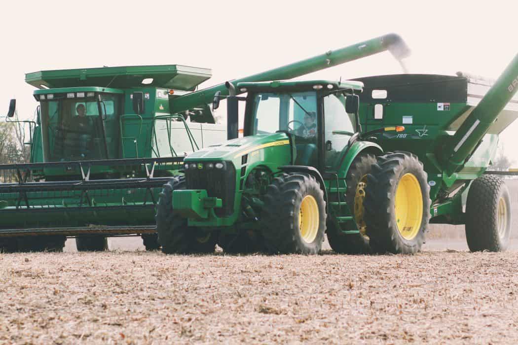 Women driving John Deere combine and grain cart tractor on a harvest day.