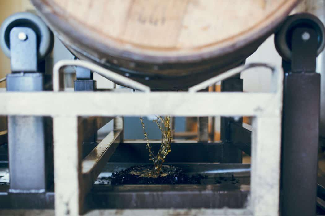 A barrel of bourbon spilling bourbon out.