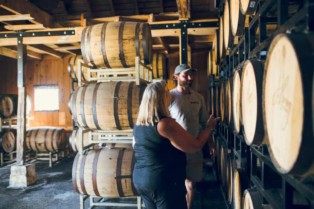 Liz and Joe Henry of J. Henry & Sons bourbon standing by barrels of bourbon.