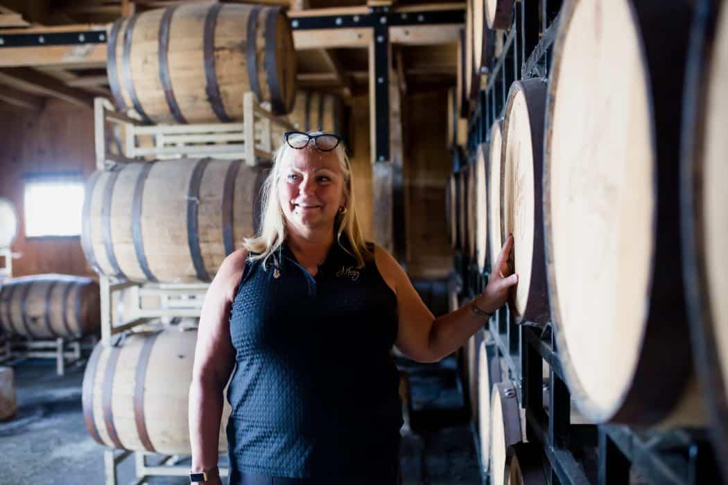 Liz Henry standing next to barrels of bourbon at J. Henry & Sons bourbon farm.