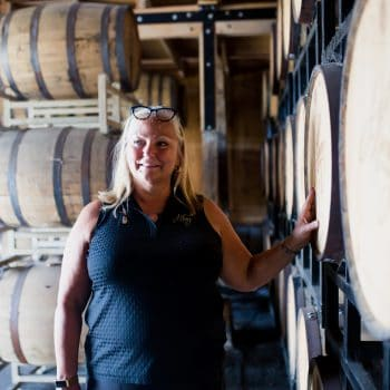 Liz Henry standing next to barrels of bourbon at J. Henry & Sons bourbon farm.