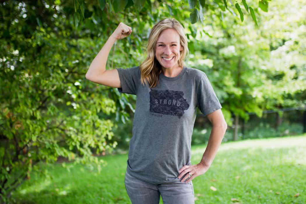 Marji Guyler-Alaniz wearing an Iowa Strong tee shirt flexing her muscles.