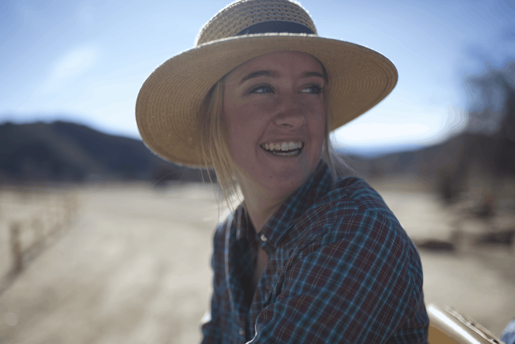 A young woman on a farm in agriculture leadership.