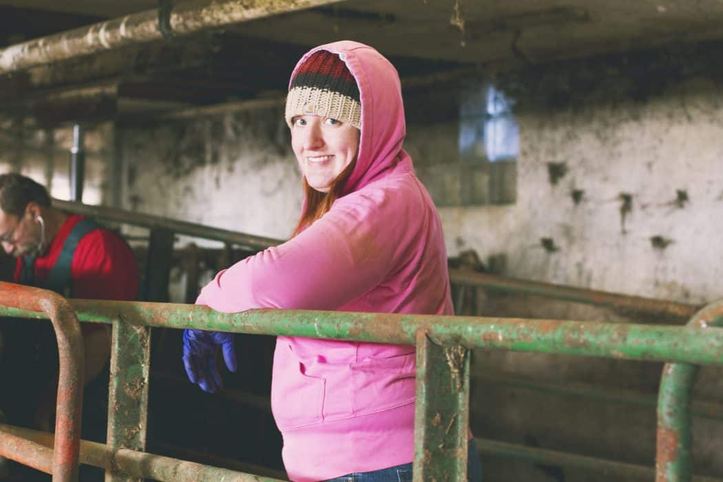 Carrie Mess, Dairy Carrie, standing in a dairy barn with a pink coat and hat on.