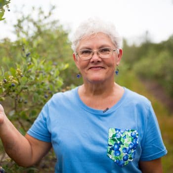 Ann Wildes, owner of the Blueberry Barn in Georgia standing in a blueberry field.