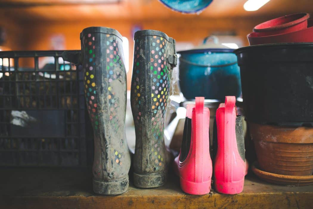 Polka dot rain boots and pink work boots sitting together on the farm.