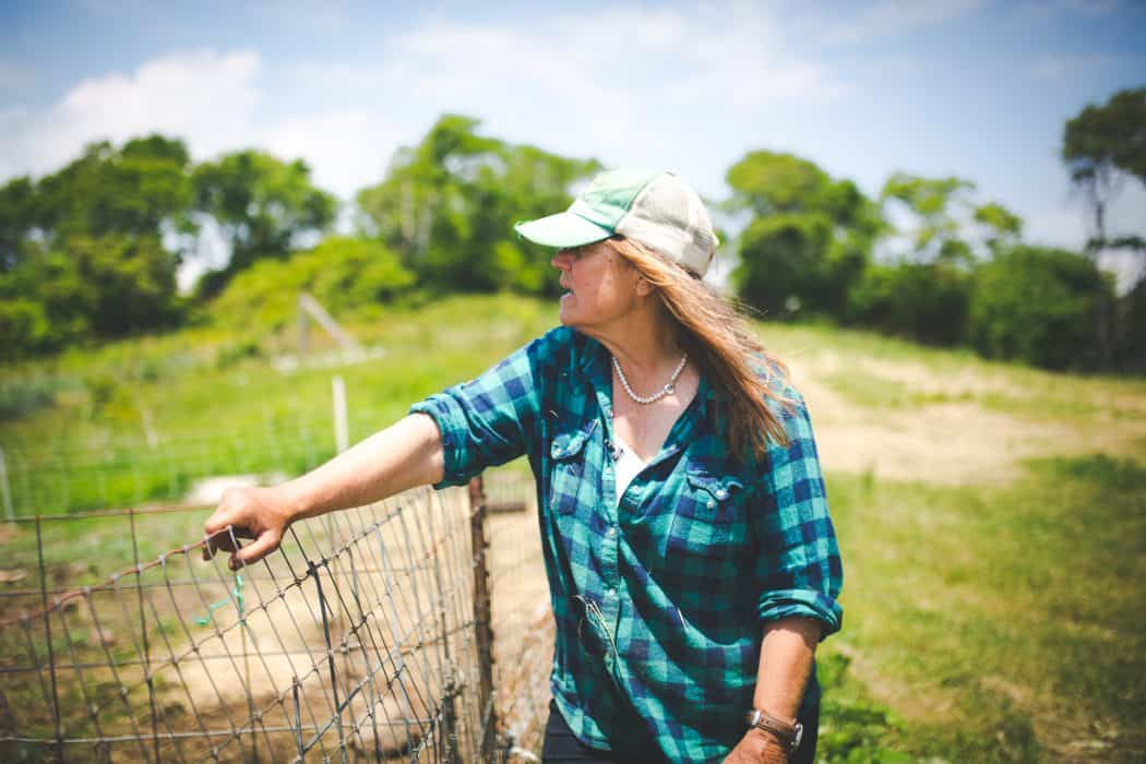 A woman on a farm leaning on a fence looking out to the pasture in a plaid shirt and baseball cap.