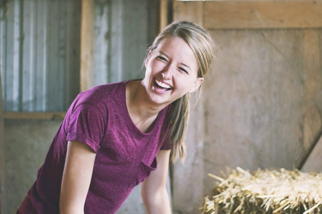 Woman smiling while standing in a barn next to hay bales.