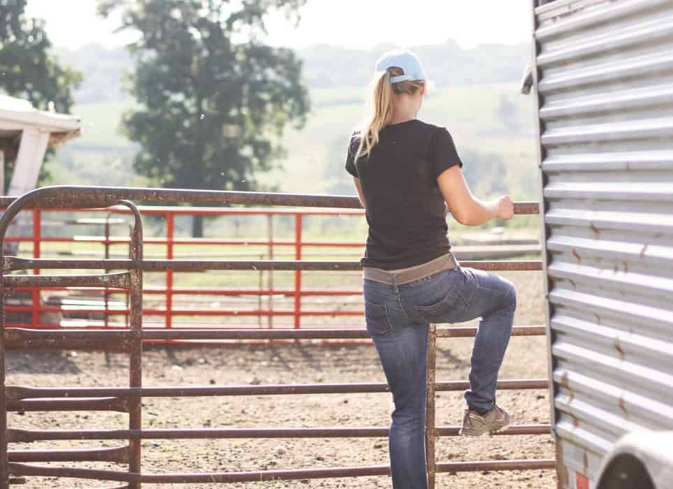 A woman climbing the fence on a farm in a black tee shirt and ball cap.