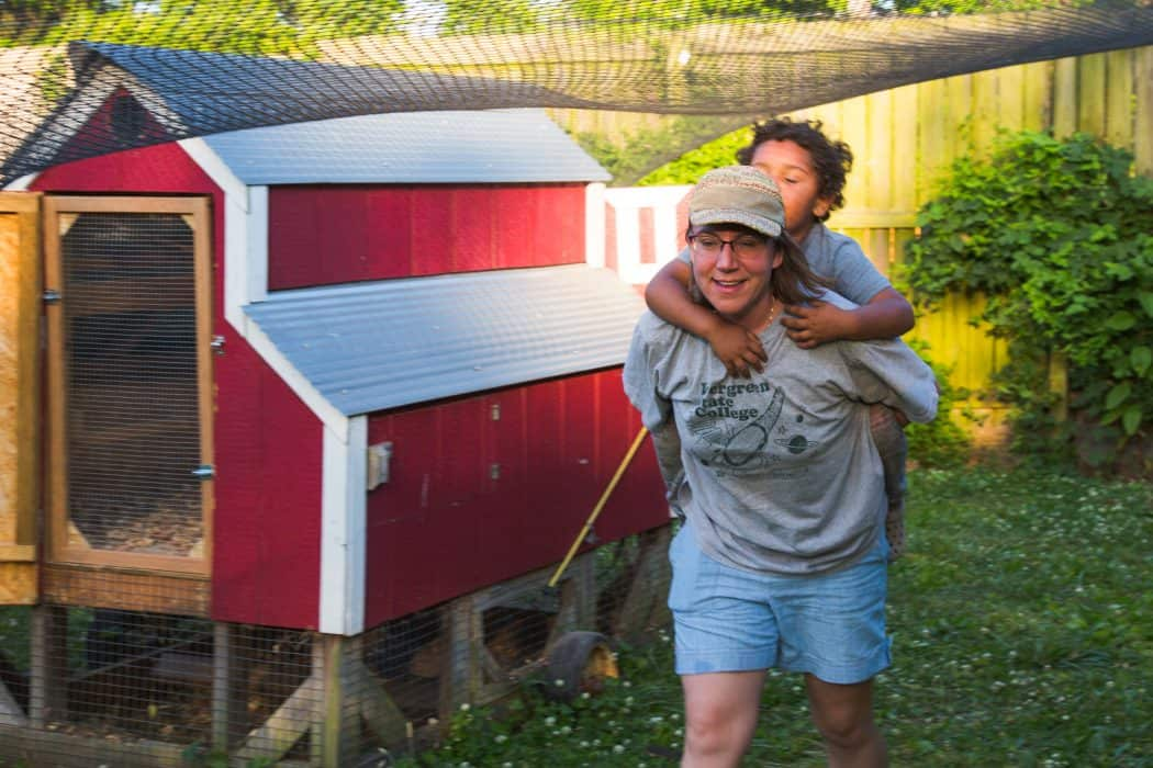 Woman giving young boy a piggy back ride on a farm near a chicken coop.