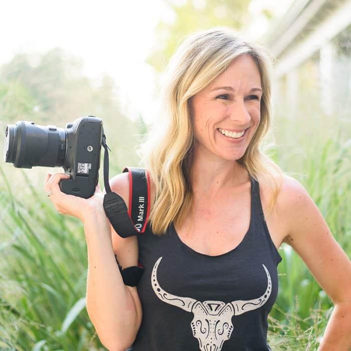 Marji Guyer-Alaniz holding her camera and smiling.
