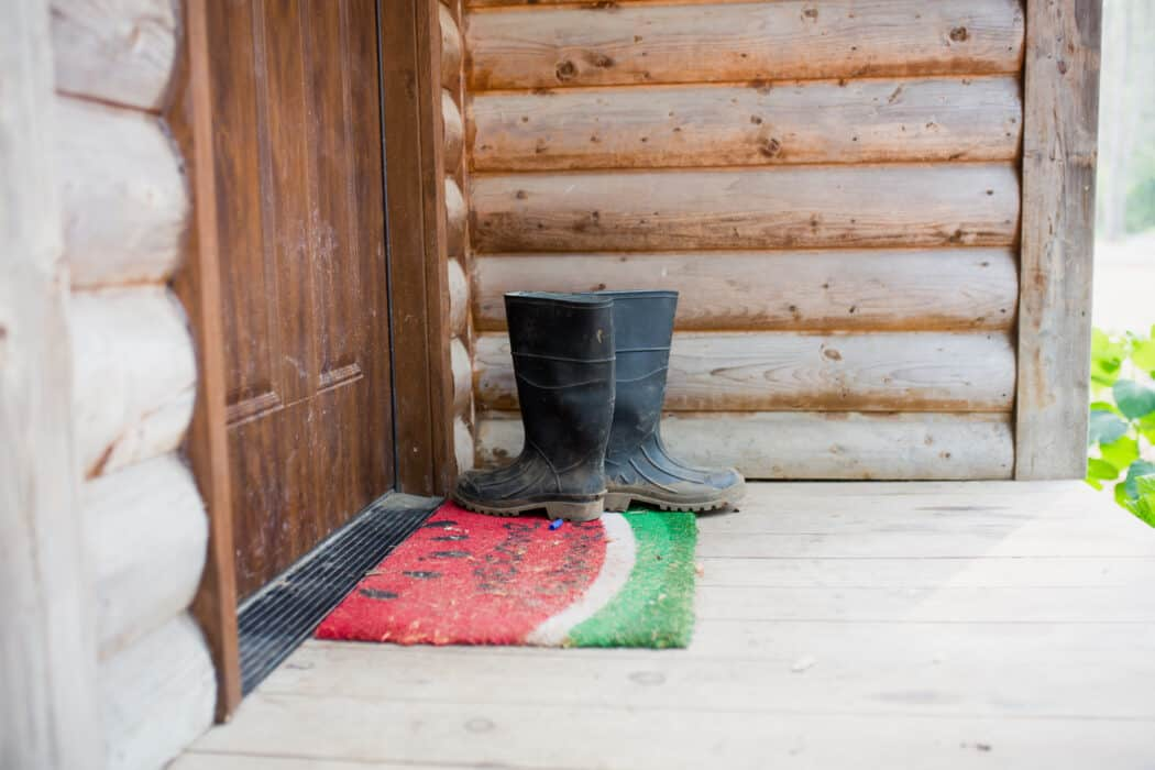 Work boots on a doorstep of a farm with a watermelon rug.