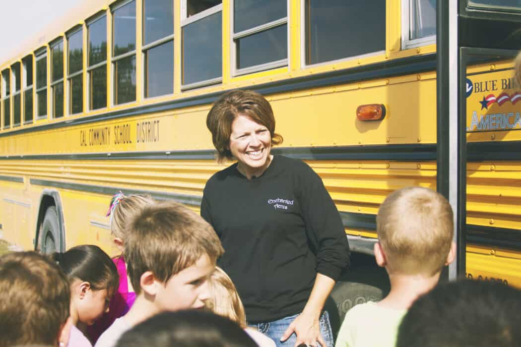 A school bus load of children greeted by woman at Enchanted Acres.