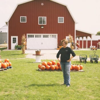 Shannon Latham, owner of Enchanted Acres, standing in front of her barn and pumpkins.